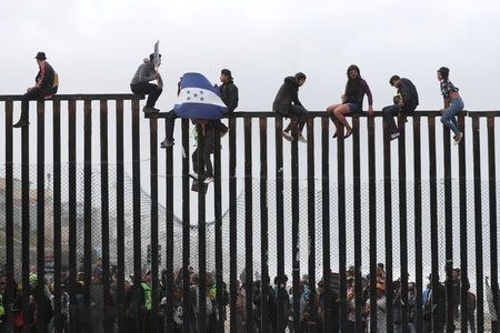 FILE PHOTO: Members of a migrant caravan from Central America and their supporters sit on the top of the U.S.-Mexico border wall at Border Field State Park before making an asylum request, in San Diego